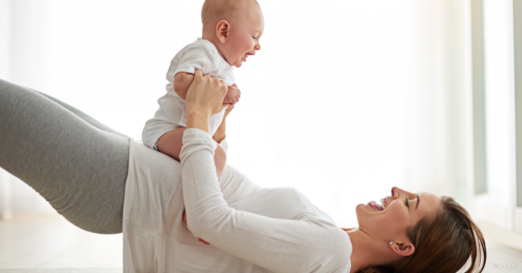 Woman laying on floor with her baby