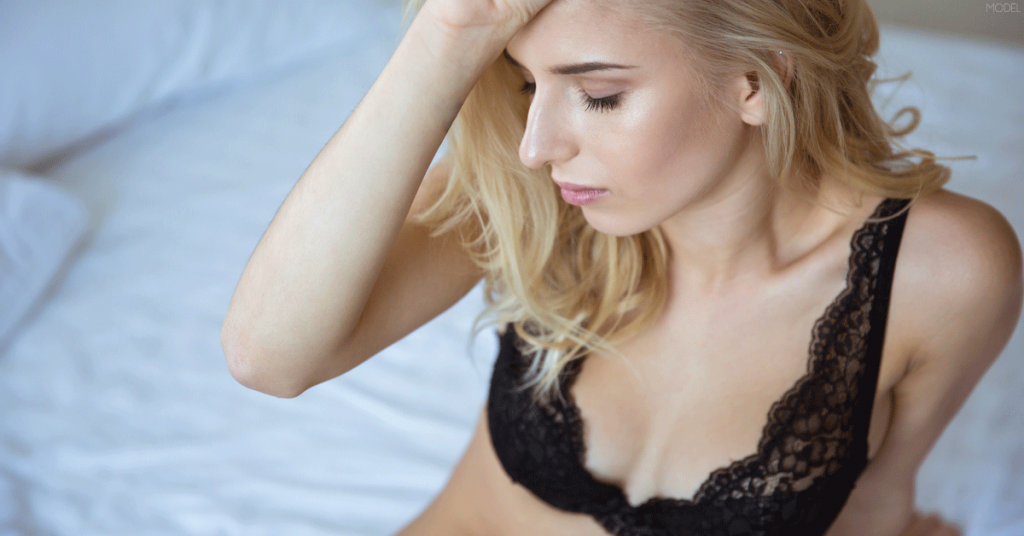 Woman in bra contemplating what needs to be done to ensure she receives great breast augmentation results