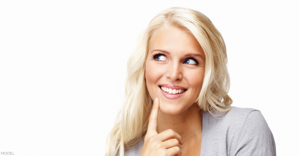 Woman thinking about whether or not it's safe to breast feed after receiving breast implants