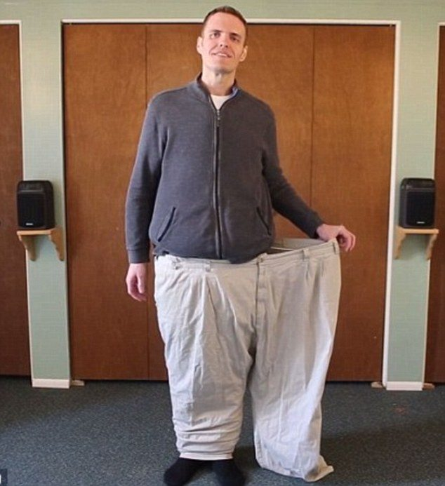 Brian Flemming wearing oversized pants stretching them out at the waist for comparison